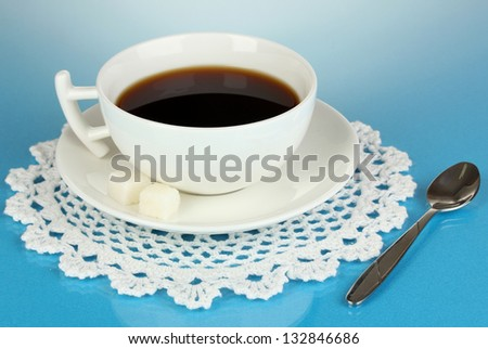 A cup of strong coffee on blue background - stock photo