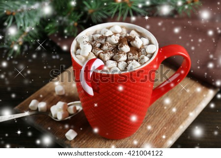 A cup of tasty cocoa and marshmallow on the table with snow effect - stock photo