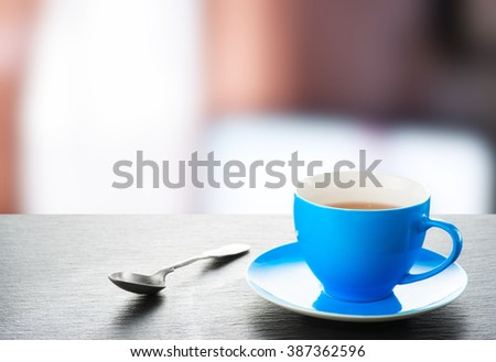 A cup of tea and a teaspoon