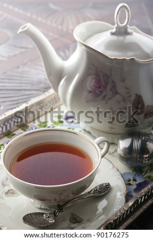 A cup of tea and a white ceramic teapot on a wooden table.  Shallow depth of field - stock photo