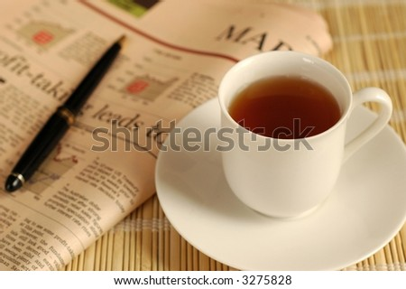 A cup of tea and business newspaper - stock photo