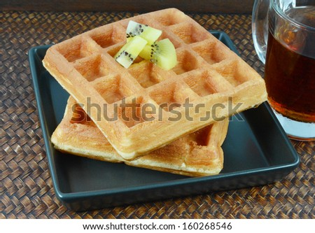 A cup of tea and waffles on the table