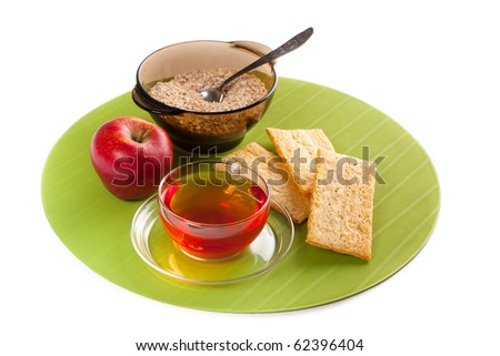 A cup of tea, crisp bread, red apple and a plate with flocks - stock photo