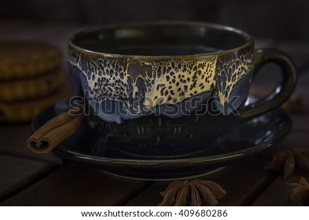 a cup of tea of glazed ceramics. On the saucer cinnamon stick.Three cookies and star anise on the table of dark wood - stock photo