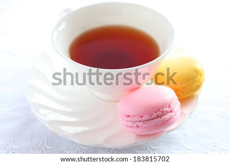 A cup of tea on a dish with some colorful macaron cookies. - stock photo