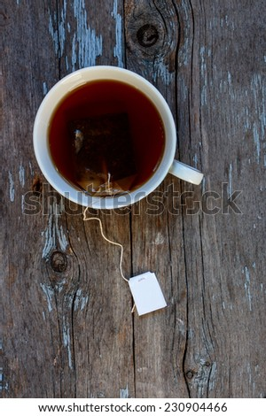 A cup of tea on a rustic wooden board, top view - stock photo