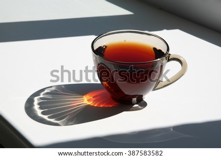 A cup of tea on the windowsill in the sunlight. - stock photo