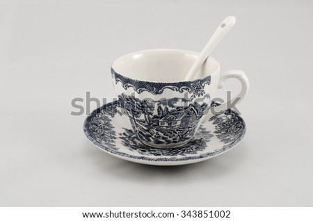 A cup of tea, spoon and saucer. English model, blue and white. - stock photo