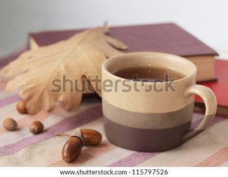 A cup of tea with autumn leaves, acorns and books - stock photo