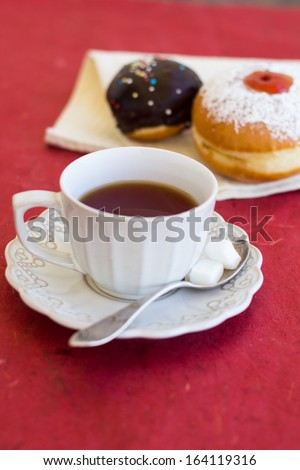 A cup of tea with fresh chocolate sufgniyot (donuts) - stock photo