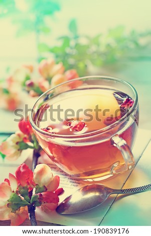 A cup of tea with red  flowers - stock photo