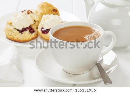 A cup of tea with scones, jam and cream. - stock photo