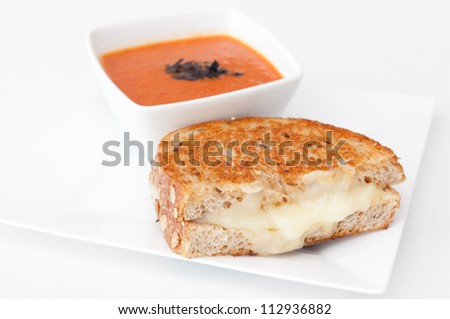 a cup of tomato soup made with fresh heirloom tomatoes and a grilled cheese sandwich made with stone ground whole wheat flour and fresh irish cheddar cheese - stock photo