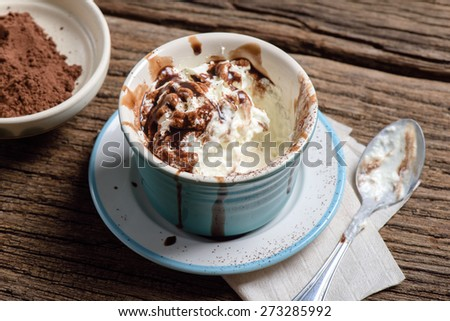 a cup of whipped cream with chocolate syrup on wooden table