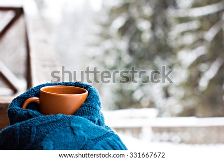 A cup with a hot drink on the background of the winter forest - stock photo