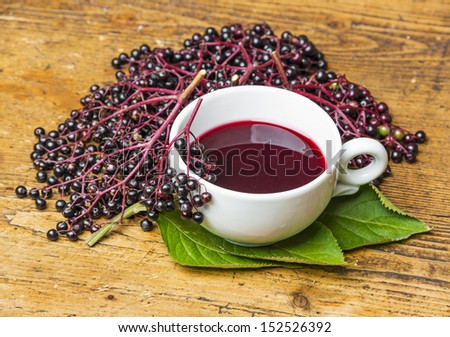 a cup with elder tea on a wooden table - stock photo