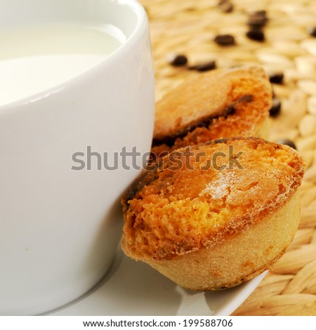 a cup with milk and some pasteis de feijao typical Portuguese pastries, on a set table - stock photo