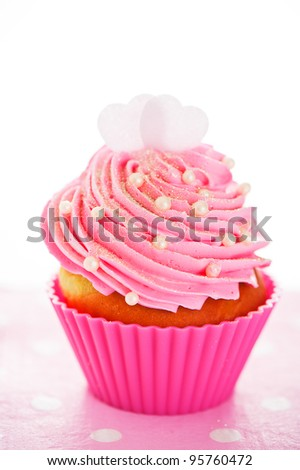 A cupcake in a pink baking cups with pink cream, white decoration and two hearts on the top on white background as a studio shoot
