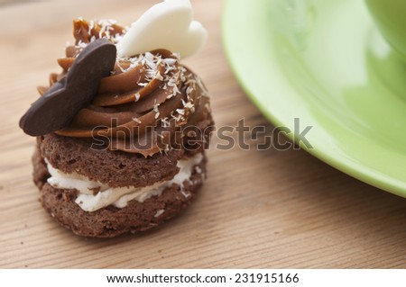 A cupcake on a table with two chocolate hearts - stock photo