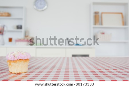 A cupcake on a tablecloth in a kitchen - stock photo