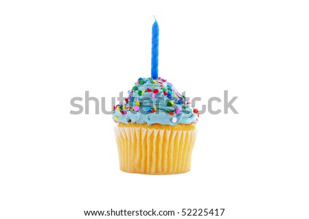 a cupcake with blue frosting, sprinkles and a candle.  isolated on white - stock photo