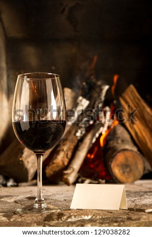 A cups of wine with fire on the background, romantic meal. Love. Write your own message. - stock photo