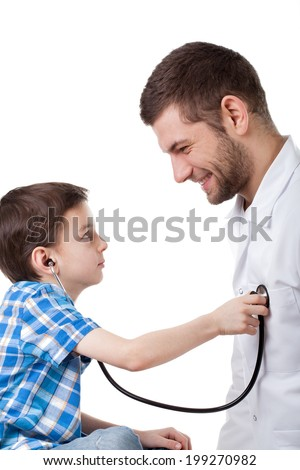 A curious little boy examining a friendly doctor using a stethoscope - stock photo