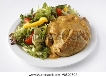 A Curry baked potato on a plate with side salad - stock photo