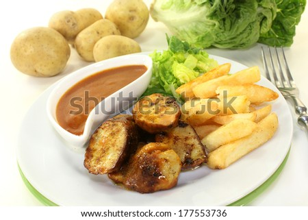 a currywurst with french fries and salad