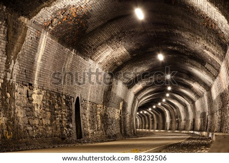 A curved tunnel in the Peak District in Derbyshire.  Originally a Victorian railway tunnel it is now part of a public footpath. - stock photo