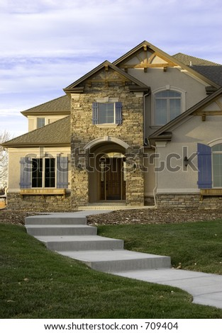 A curved walkway leads a path toward a high end custom built home. - stock photo