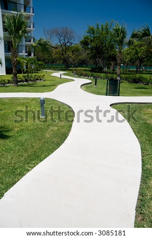 A curvy concrete path going through the grounds of a tourist resort - stock photo