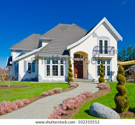 A custom built luxury house in a residential neighborhood. This high end home is very nicely landscaped property. - stock photo