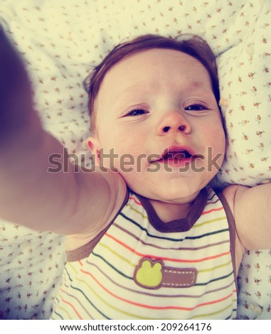 a cut boy laughing on a blanket inside toned with a retro vintage instagram filter  - stock photo