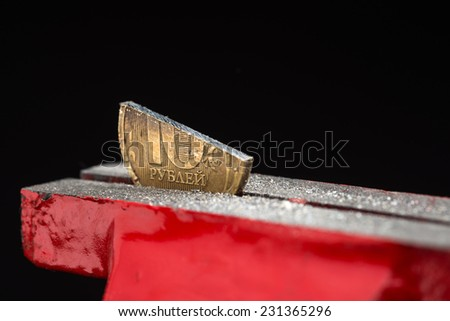 A cut ten rubles half-coin squeezed in a metal vise tool, concept of inflation and financial crisis in Russian Federation. - stock photo