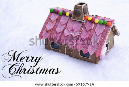 A cute and tasty looking gingerbread house on top of some snow. - stock photo