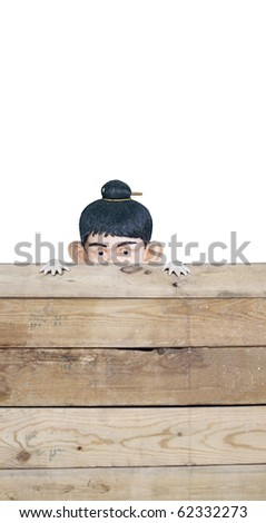 A cute Asian baby doll looking over a timber fence. Lots of copyspace and room for text on this isolate. - stock photo