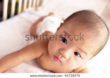 A cute asian baby laying stomach down on the bed. - stock photo
