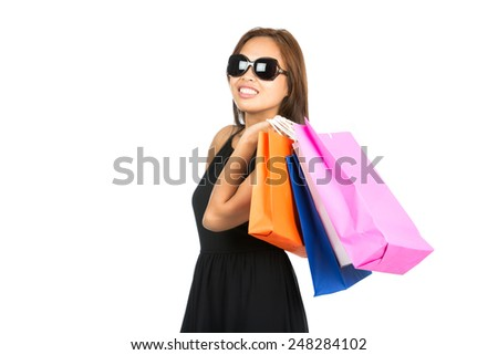 A cute Asian female shopaholic in sunglasses, stylish black dress has fun with colorful department store shopping bags flung over shoulder looking away with a smile. Thai national of Chinese origin - stock photo
