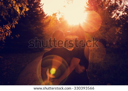 a cute attractive couple looking towards the sunset at a park with a toned retro instagram filter - stock photo