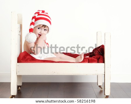 A cute baby boy eating a candy cane in a little bed - stock photo