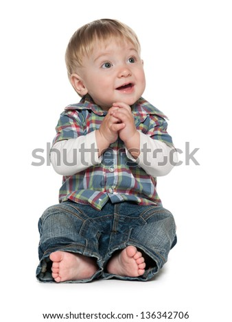 A cute baby boy is sitting on the white background - stock photo