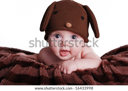 A cute baby boy wearing a puppy hat - stock photo
