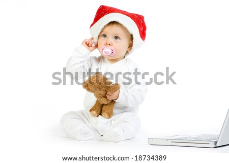A cute baby girl wearing a Christmas cap, playing with a teddy and a laptop.