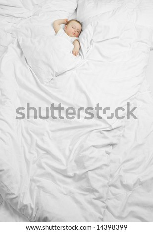 A cute baby sleeping on a huge bed with white sheets - stock photo