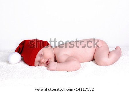 A cute baby sleeping wearing a santa hat - stock photo