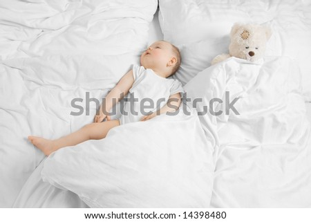 A cute baby sleeping with a teddy on a clean white bed - stock photo