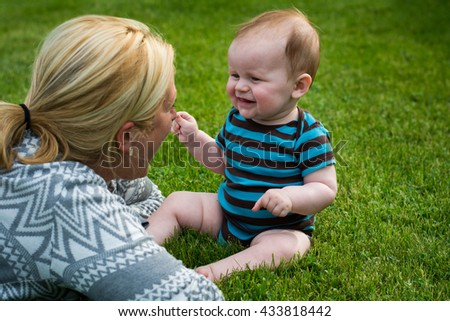 A Cute Baby Smiling at a Young Woman in the Grass - stock photo