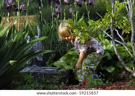 A cute blond girl plays in the garden in the early evening. - stock photo