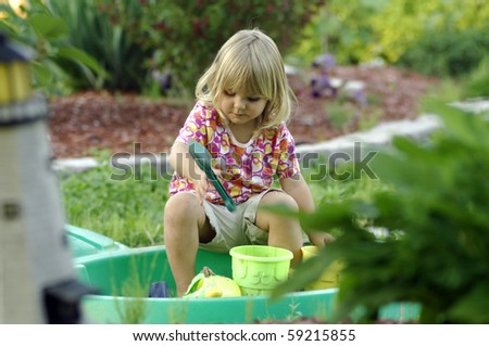 A cute blond girl plays in the garden in the early evening.